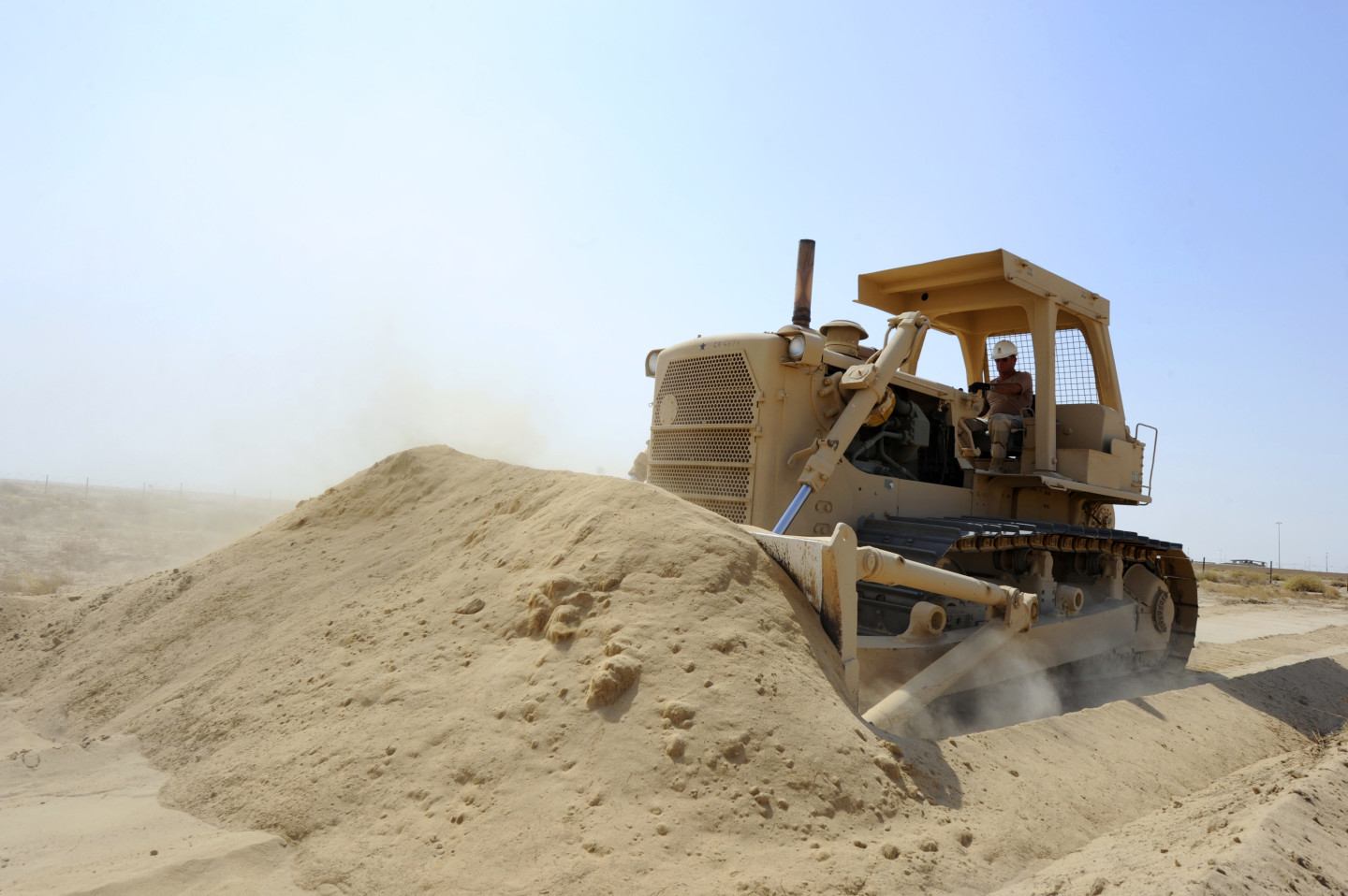 110705-N-WL435-178 KUWAIT NAVAL BASE, Kuwait (July 5, 2011) Master Chief Equipment Operator Charles Boris, assigned to Task Group (TG) 56.2, pushes sand with a bulldozer to reinforce an existing berm at a joint forces weapons training range in Kuwait. TG 56.2 naval construction forces provide expeditionary engineering and construction support for forward deployed forces in the U.S. 5th Fleet area of responsibility. (U.S. Navy photo by Mass Communication Specialist 1st Class Peter D. Lawlor/Released)